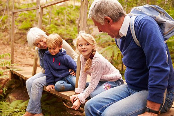Grandparents sitting with grandkids on wooden bridge